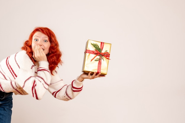 Front view of young woman with christmas present on a white wall