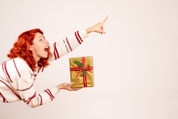 Front view of young woman with christmas present on the white wall