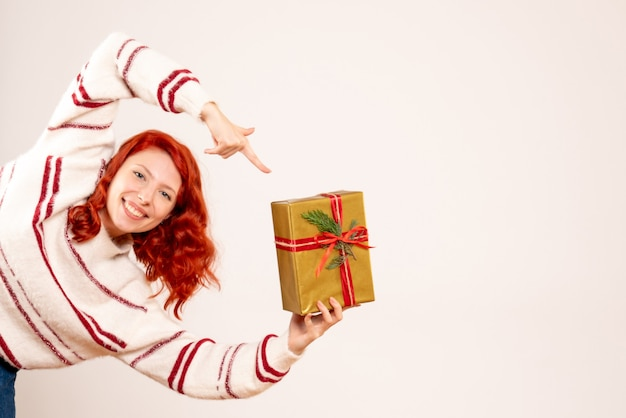 Front view of young woman with christmas present on white wall