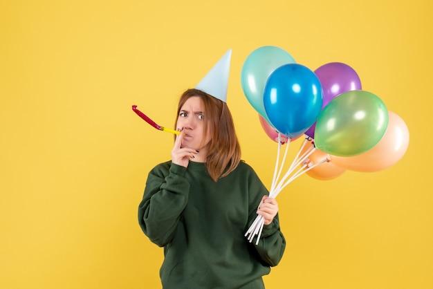 カラフルな風船と正面図の若い女性