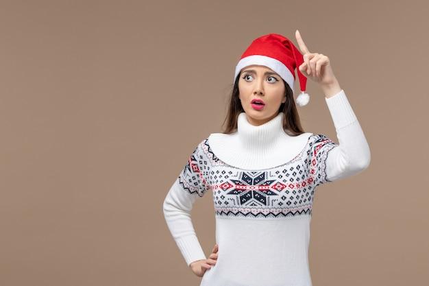 갈색 배경 새 해 감정 크리스마스에 혼란 된 표정으로 전면보기 젊은 여자