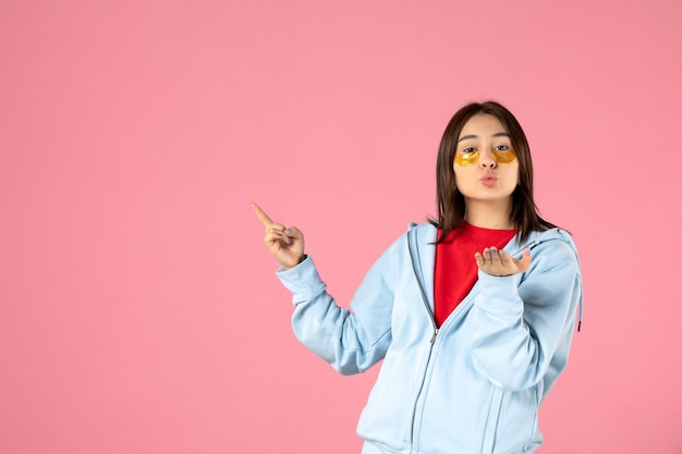 Front view of young woman with eye patches under her eyes on pink wall