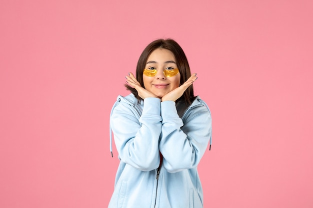 Front view of young woman with eye patches under her eyes posing on pink wall
