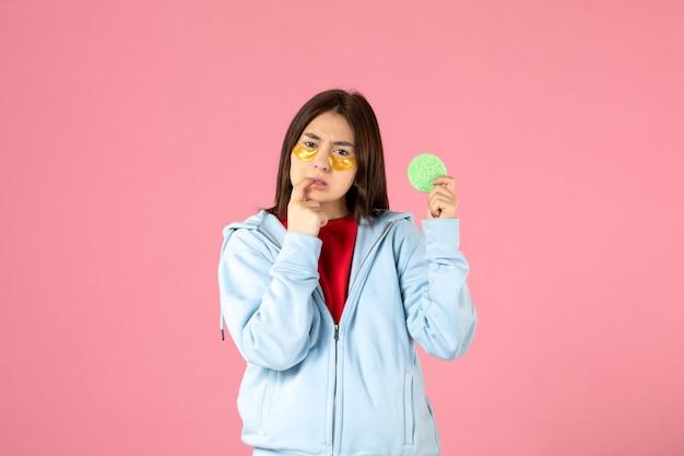 Vista frontale della giovane donna con bende per gli occhi e piccola spugna sul muro rosa