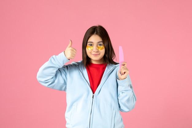 Vista frontale della giovane donna con bende per gli occhi e lima per unghie sul muro rosa