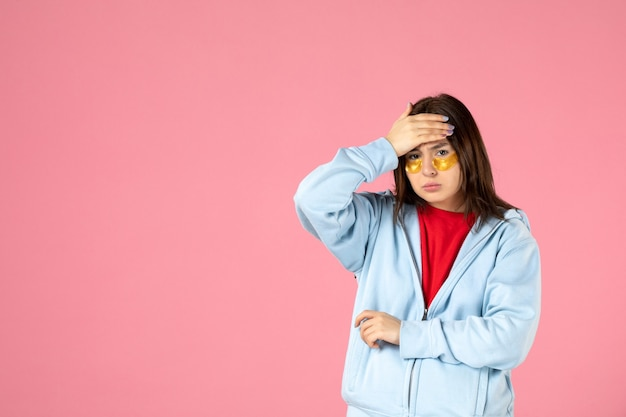 Front view of young woman with eye patches on pink wall