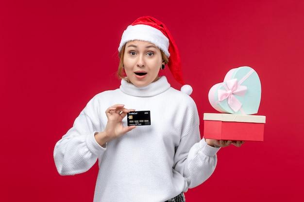 Вид спереди молодая женщина с подарками и банковской картой на красном столе