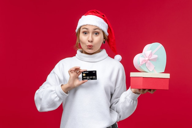 Front view young woman with gifts and bank card on the red background