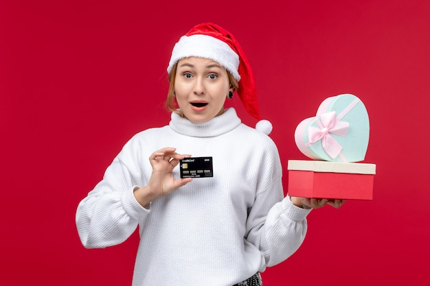 Front view young woman with gifts and bank card on red desk