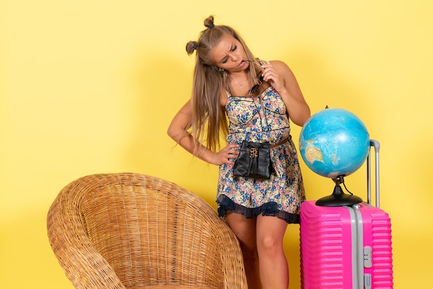 Front view of young woman with globe and pink bag in summer vacation on a yellow wall