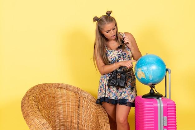 Vista frontale della giovane donna con globo e borsa rosa durante le vacanze estive sulla parete gialla
