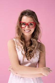 Vista frontale della giovane donna con gli occhiali a forma di cuore