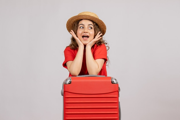 Vista frontale giovane donna con la sua valigia in piedi