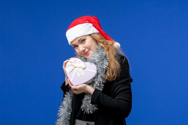 Front view of young woman with holiday present on blue wall