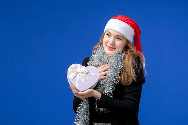 Vista frontale della giovane donna con regalo di festa sulla parete blu