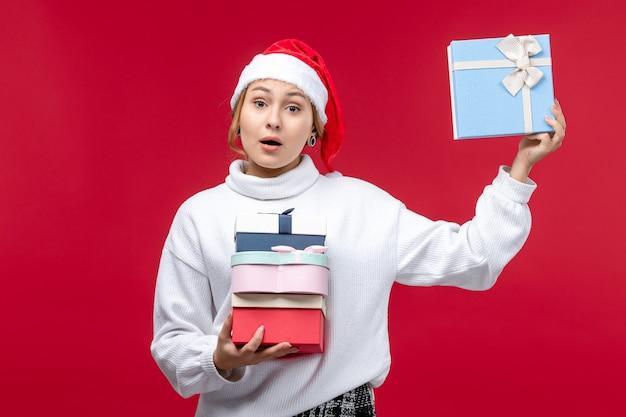 赤い背景に休日のプレゼントと正面図若い女性