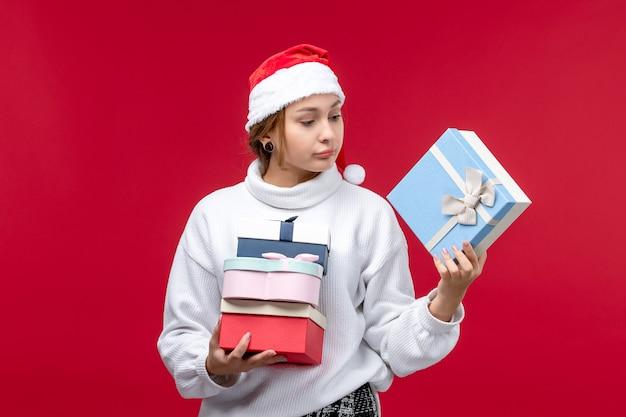 赤い机の上に休日のプレゼントと正面図の若い女性