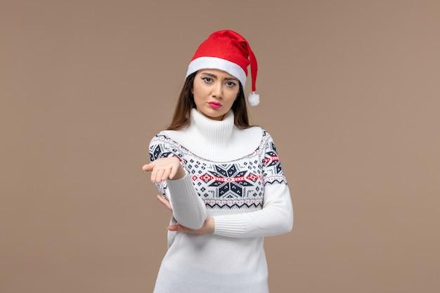 Вид спереди молодая женщина с безумным выражением лица на коричневом фоне рождественские эмоции новый год