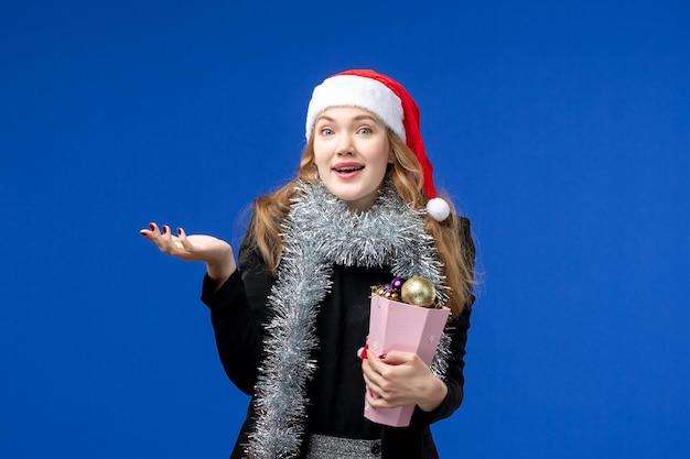 Vista frontale della giovane donna con i giocattoli dell'albero di capodanno sulla parete blu