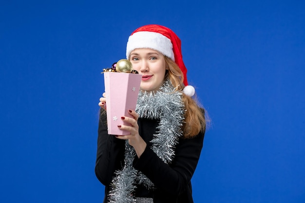 Front view of young woman with new year's tree toys on blue wall