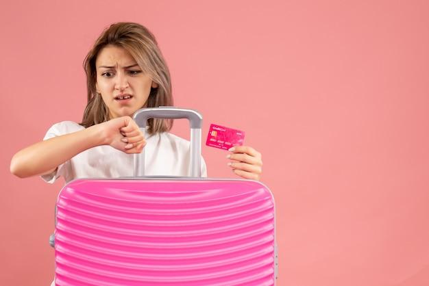 時間をチェックする地図を保持しているピンクのスーツケースを持つ正面の若い女性