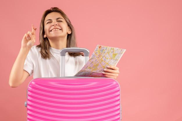 Giovane donna di vista frontale con la mappa rosa della tenuta della valigia che fa il segno di desiderio