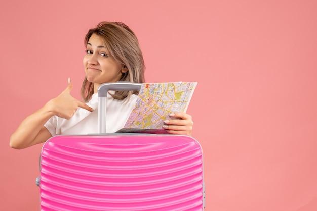 自分自身を指している地図を保持しているピンクのスーツケースを持つ若い女性の正面図