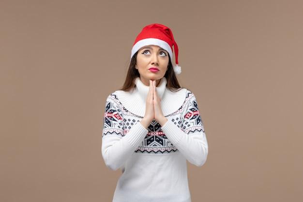 Giovane donna di vista frontale con espressione di preghiera sullo sfondo marrone natale emozione nuovo anno