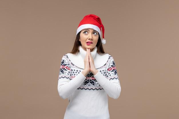 Giovane donna di vista frontale con espressione di preghiera su sfondo marrone natale emozioni capodanno