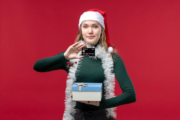 赤い背景にプレゼントと銀行カードを持つ正面図