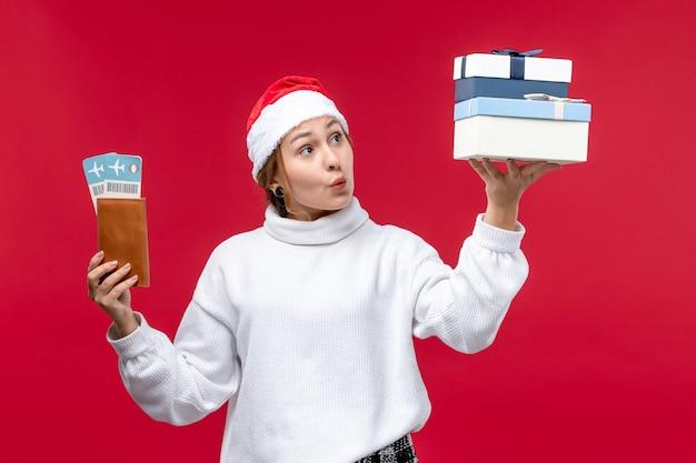 Молодая женщина вид спереди с подарками и билетами на красном фоне