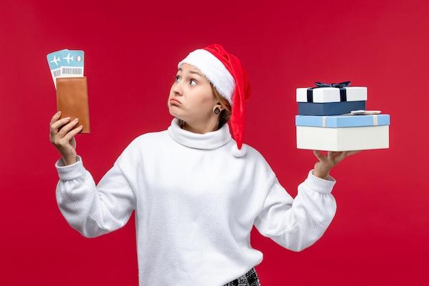 Giovane donna di vista frontale con regali e biglietti sullo scrittorio rosso