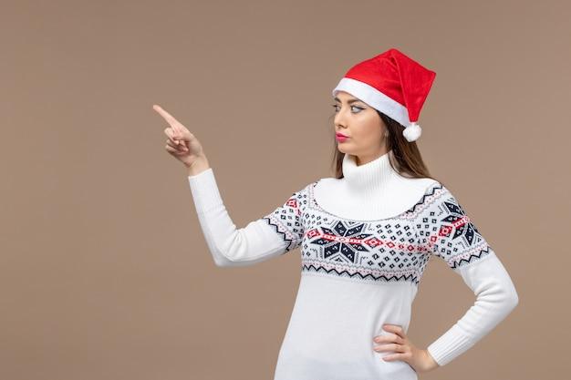 Giovane donna di vista frontale con il mantello rosso sul natale di emozione del nuovo anno del fondo marrone