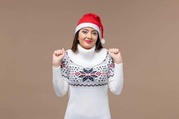 Вид спереди молодая женщина с красной рождественской шапкой на коричневом столе рождественские эмоции новый год