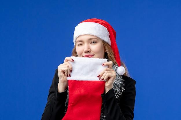 Vista frontale della giovane donna con il calzino rosso delle vacanze sulla parete blu