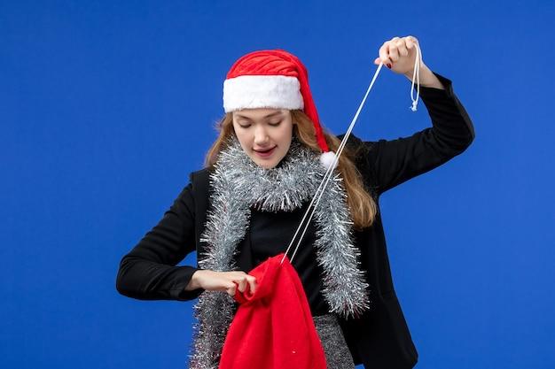 Vista frontale della giovane donna con la borsa regalo rossa sulla parete blu
