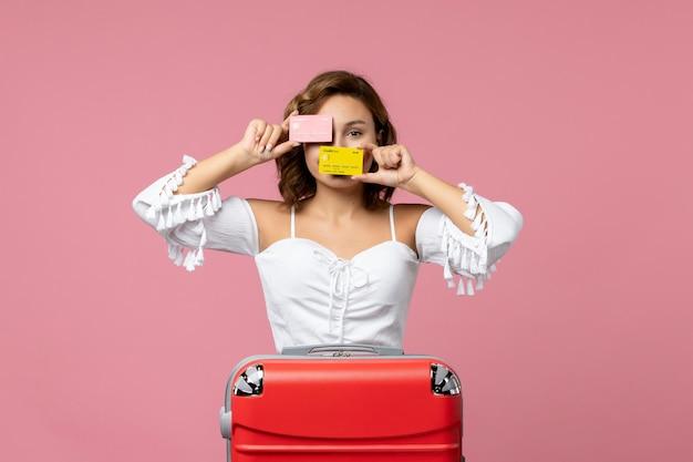Vista frontale della giovane donna con la borsa da vacanza rossa che tiene le carte bancarie sul muro rosa