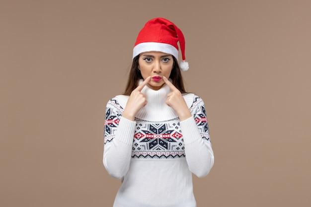 Giovane donna di vista frontale con l'espressione triste sul nuovo anno marrone di natale di emozione del fondo