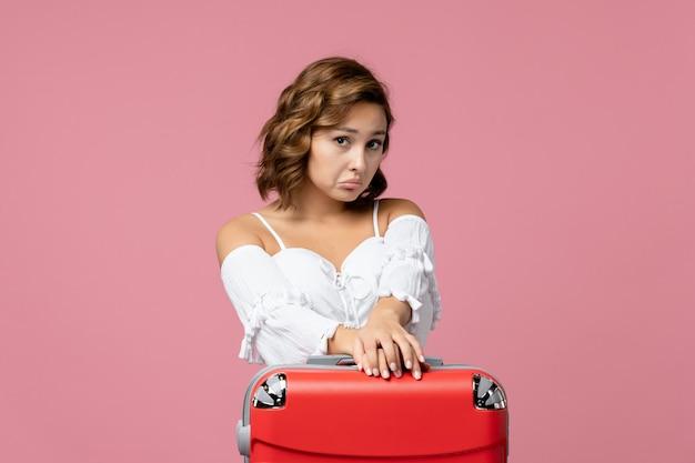 Vista frontale della giovane donna con la faccia triste sul muro rosa