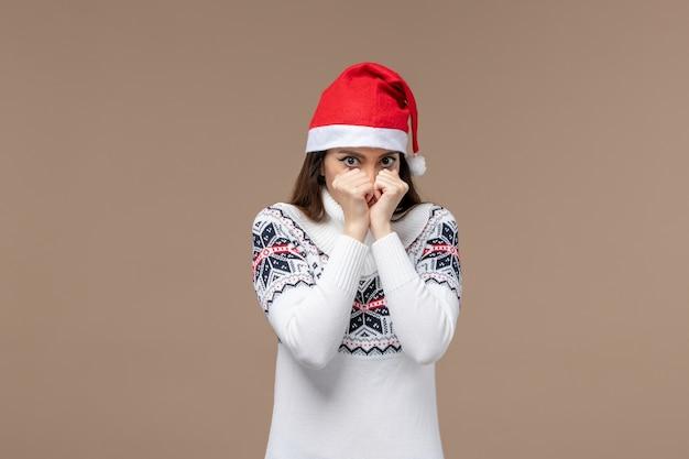Giovane donna di vista frontale con espressione spaventata su sfondo marrone emozione natale capodanno
