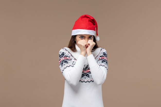 茶色の背景感情クリスマス新年の怖い表情を持つ正面図若い女性