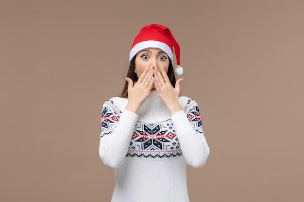 Giovane donna di vista frontale con l'espressione sconvolta sul natale di emozione del nuovo anno del fondo marrone