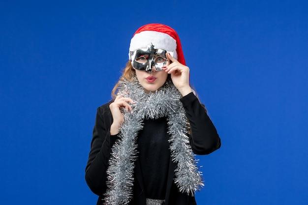 Vista frontale della giovane donna con maschera d'argento sulla parete blu