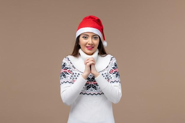 Giovane donna di vista frontale con espressione sorridente su sfondo marrone natale capodanno emozione