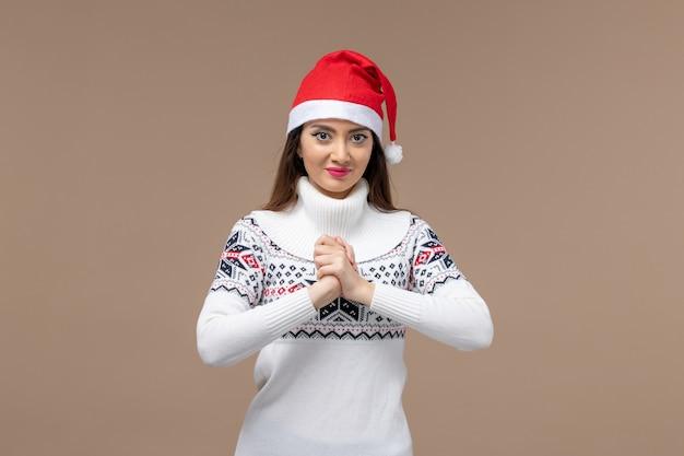 Вид спереди молодая женщина с улыбающимся выражением лица на коричневом фоне рождественские эмоции новый год