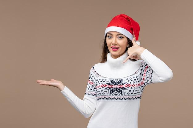 茶色の背景の休日の感情のクリスマスに笑顔の表情を持つ若い女性
