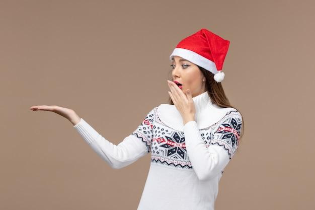 Giovane donna di vista frontale con l'espressione sorpresa sul natale marrone di emozione di festa del fondo