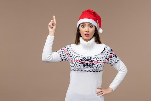 Giovane donna di vista frontale con l'espressione sorpresa sul natale marrone di emozione del nuovo anno del fondo