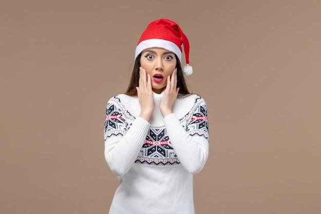 Giovane donna di vista frontale con l'espressione sorpresa sul nuovo anno marrone di emozione di natale dello scrittorio