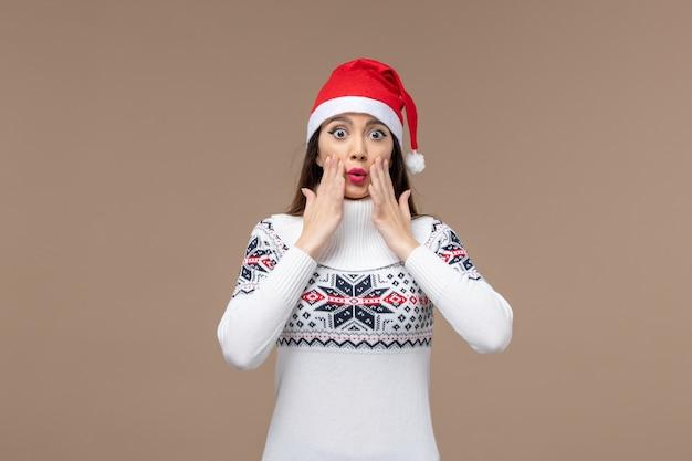 Giovane donna di vista frontale con il fronte sorpreso sul natale di emozioni del nuovo anno del fondo marrone